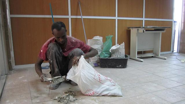 Eritrean worker renovating Likud offices (Photo: Zvika Tishler)