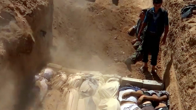 Mass grave near Damascus (Photo: AFP PHOTO / YOUTUBE / LOCAL COMMITTEE OF ARBEEN)