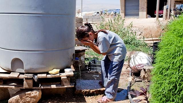"""שוטפת את הפנים עם מים ממיכל גדול המוצב מחוץ לביתה. מים לשתייה מגיעים אל הפליטים דרך מקור מים מקומי (צילום: ס. בולדווין, סוכנות האו""""ם לפליטים) (צילום: ס. בולדווין, סוכנות האו"""