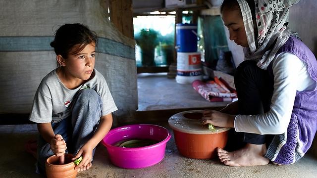 """עוזרת לאחותה הגדולה, חודוד, להכין ארוחת ערב בזמן חודש הרמדאן (צילום: ס. בולדווין, סוכנות האו""""ם לפליטים) (צילום: ס. בולדווין, סוכנות האו"""