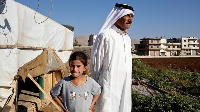 """מוחמד, אביה המובטל והחולה של איה, מחוץ לביתם הבנוי מעץ ומיריעות פלסטיק (צילום: ס. בולדווין, סוכנות האו""""ם לפליטים) (צילום: ס. בולדווין, סוכנות האו"""