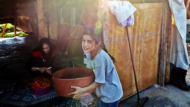 """עוזרת לאחות נוספת, חאלה, להכין מיץ גזר בביתם הצנוע (צילום: ס. בולדווין, סוכנות האו""""ם לפליטים) (צילום: ס. בולדווין, סוכנות האו"""