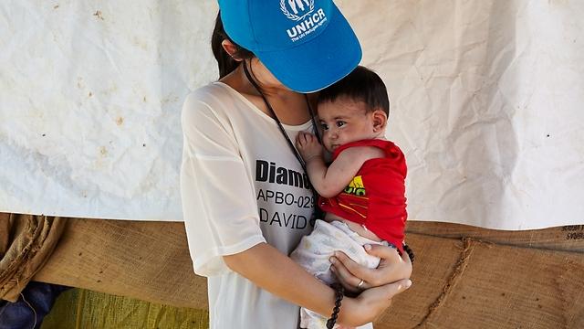 """חברת צוות סוכנות האו""""ם לפליטים, יוג'ין ביון, מחזיקה בידיה את רודיק, פעוט בן ארבעה חודשים, במחנה לא רשמי בטרבול בבקעת הלבנון. """"כל פליט סורי שפגשתי קיבל אותי בזרועות פתוחות, בהם גם רודיק"""" (צילום: ס. בולדווין, סוכנות האו""""ם לפליטים) (צילום: ס. בולדווין, סוכנות האו"""