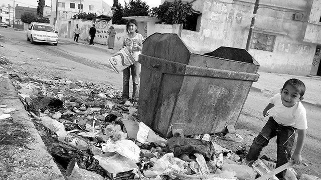 """עיישה בת ה-11 ועבדול-קאדר בן ה-6 תרים בזבל אחר אלומיניום, פלסטיק וחומרים אחרים שיוכלו למכור כדי לשלם שכר דירה על ביתם (צילום: ג'יי. קולר, סוכנות האו""""ם לפליטים) (צילום: ג'יי. קולר, סוכנות האו"""