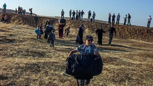 """נער סורי נושא את תיקו וחוצה את הגבול מסוריה לירדן (צילום: ע. לבן-מטי, סוכנות האו""""ם לפליטים) (צילום: ע. לבן-מטי, סוכנות האו"""