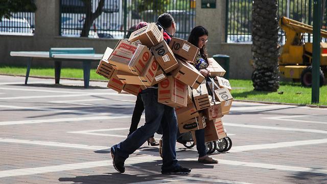 מעמיסים ערכות מגן בקריית מוצקין, היום (צילום: אבישג שאר-ישוב)