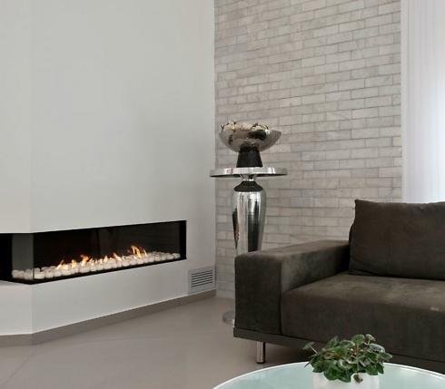 ספה בגוון אפור כהה, חיפוי לבנים בגווני אפור ולבן וקמין בעיצוב מודרני בסלון (צילום: עודד סמדר) (צילום: עודד סמדר)