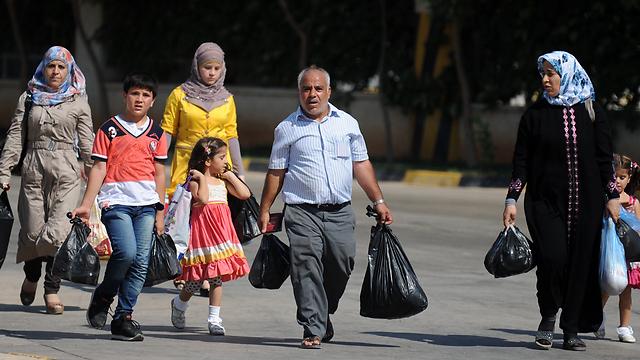 פליטים סורים חוצים את הגבול לטורקיה בסמוך לעיר רייחאנלי (צילום: AFP) (צילום: AFP)