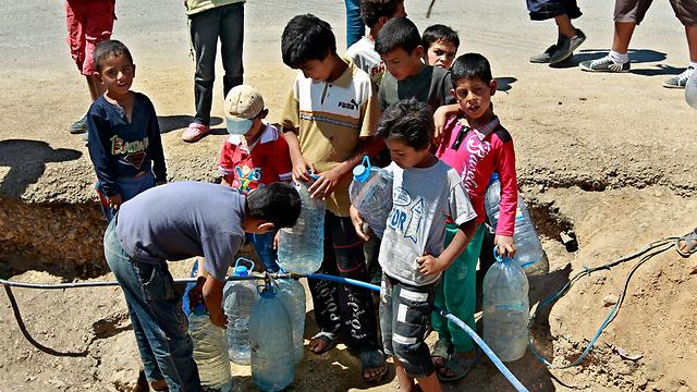 ילדים סורים ממלאים מכלים במי שתייה. מחנה פליטים בעיר פאהור בלבנון (צילום: AP) (צילום: AP)