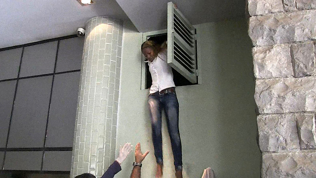 Hostage escaping through a vent (Photo: AFP)