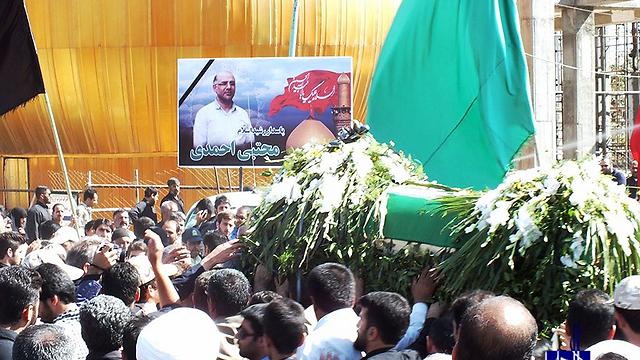 התמונות מהאתר האיראני של לוויית אחמדי. תמונתו נישאת מעל ארונו ()