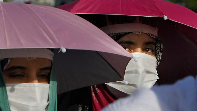 מתפללות מכסות את פיהן כדי להיזהר מהווירוס הנשימתי שהתפשט בסעודיה (צילום: AP) (צילום: AP)