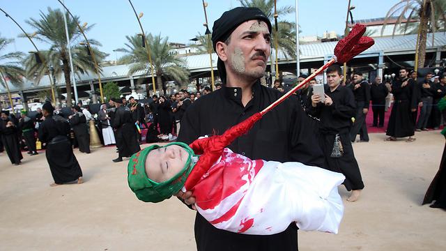 תינוק שיעי בעיראק מוצג בתור בן האימאם חוסיין, שנהרג כילד עם אביו מפגיעת חץ בגרונו בקרב כרבאלא (צילום: AFP) (צילום: AFP)
