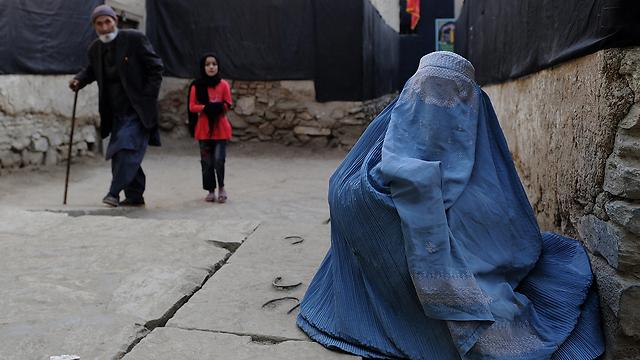 אישה לבושה בבורקה מקבצת נדבות בכניסה למסגד באפגניסטן (צילום: AFP) (צילום: AFP)