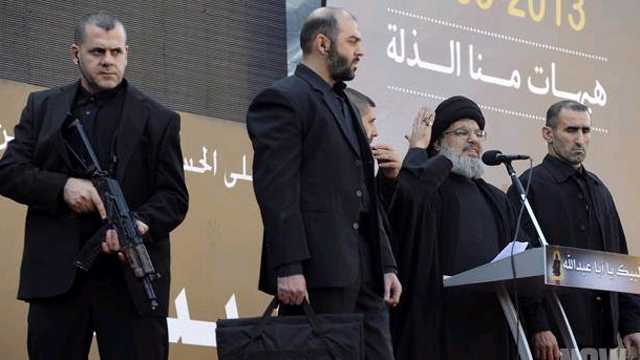 Nasrallah on stage with unarmed bodyguard carrying the suitcase