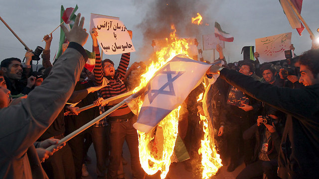 Iranian students burn an Israeli flag outside the Fordo facility (Photo: EPA)