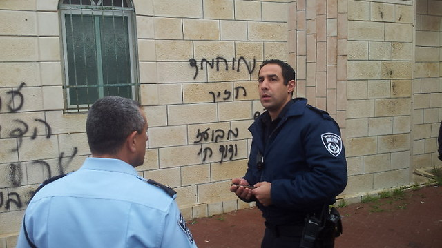 Police officer walks by 'Mohammed is a pig' graffiti  (Photo: Hassan Shaalan)
