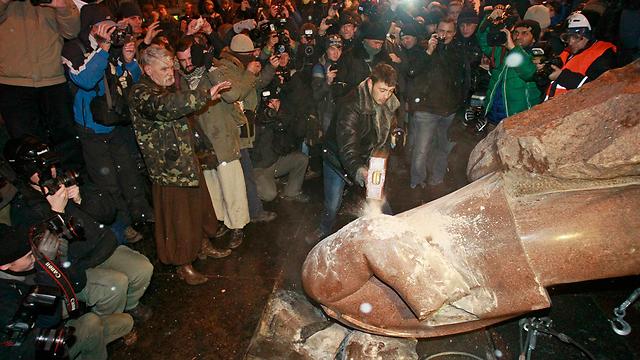 מפגינים מחריבים את דמותו של לנין בהפגנות בקייב (צילום: רויטרס)