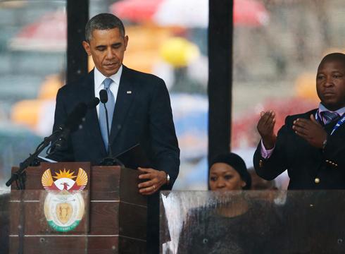 """קרוב מאוד לאובמה. המתורגמן בטקס האשכבה למנדלה לצד נשיא ארה""""ב (צילום: AP)"""