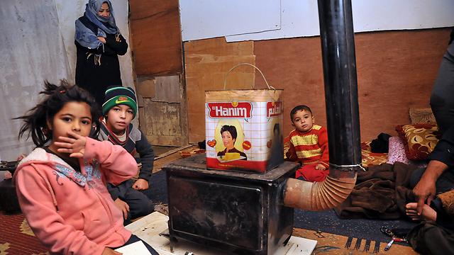 Children huddle around heater in refugee camp (Photo:AFP) (Photo: AFP)