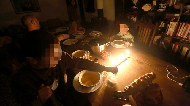 Without power, family eats in dark (Photo: Gil Yohanan)