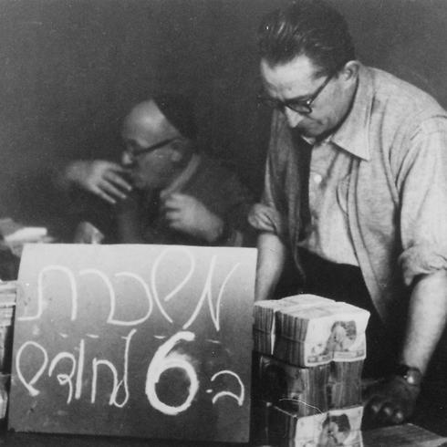 """חלוקת השכר בראשית שנות ה-50 ע""""י הגזבר, קרול שניידר (צילום: ארכיון רמב""""ם) (צילום: ארכיון רמב"""