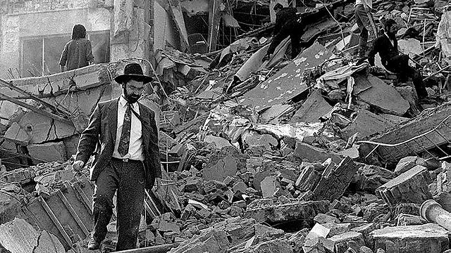 Jewish Argentine man treading through the wreckage of the bombing (Photo: AFP)