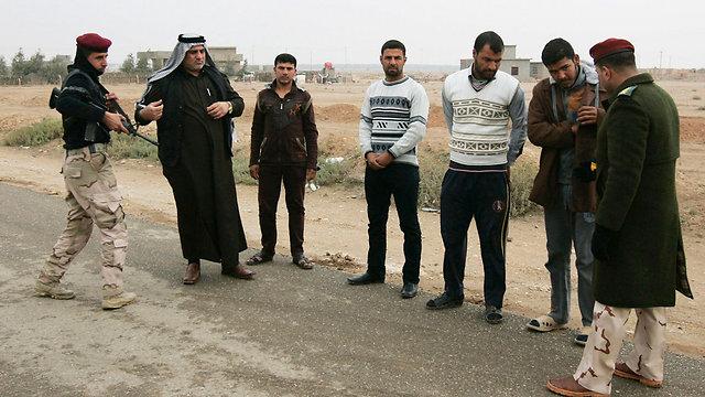 שוטר עיראקי בודק אזרחים שנמלטו מפלוג'ה ורמאדי (צילום: רויטרס) (צילום: רויטרס)
