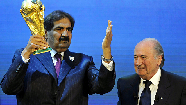 The Emir of Qatar (left) receiving the World Cup from the president of FIFA (Photo: EFP)