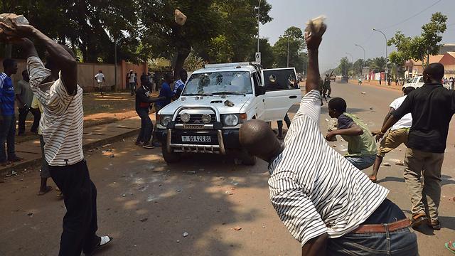 תושבים מיידים אבנים על מכונית ובה שני ילדיו של קולונל סלקה לשעבר (צילום: AFP) (צילום: AFP)