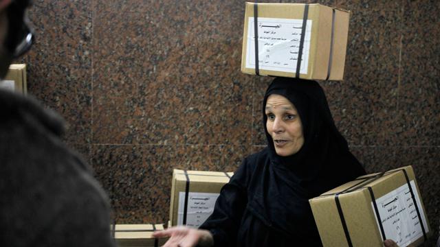 A woman carrying referendum ballots (Photo: AP) (Photo: AP)