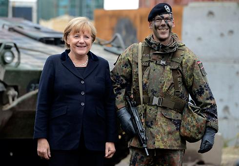 במקור, השירות האזרחי נועד ללכת לקראת סרבני המצפון. מרקל לצד חייל גרמני (צילום: רויטרס)