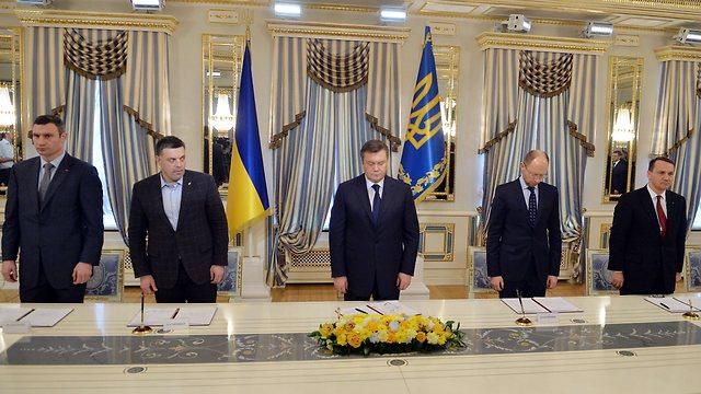 ינוקוביץ' חמור הסבר ומנהיגי האופוזיציה במעמד חתימת ההסכם (צילום: AFP) (צילום: AFP)