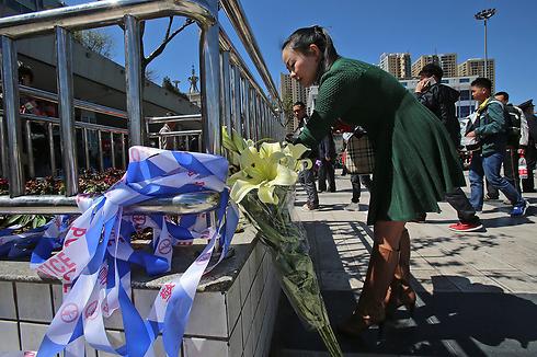 אישה מניחה פרחים לזכר הנרצחים, הבוקר (צילום: EPA) (צילום: EPA)