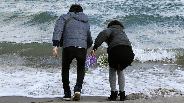 משליכים פרחים לים לזכר הנספים. מינמיסומה, פוקושימה (צילום: AP)