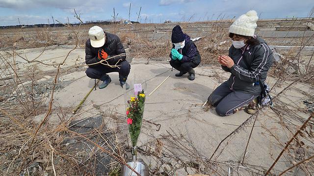קרובי משפחה של הרוגי הצונאמי בניימי, ליד המתחם הגרעיני בפוקושימה (צילום: AFP)