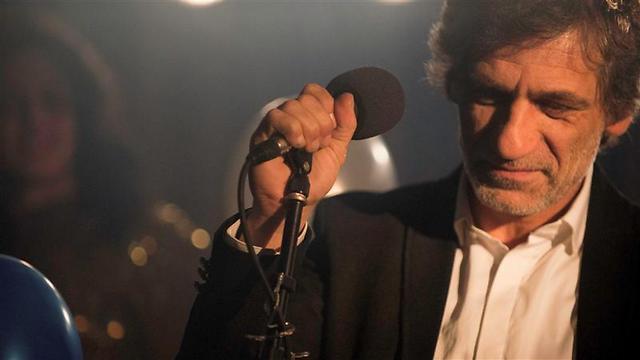 """אלון אבוטבול כזאב במהלך ביצוע של השיר """"משחק של דמעות"""" בסרט ()"""