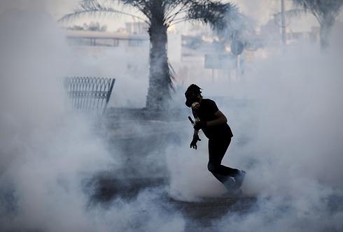 """השיעים התקוממו ב""""אביב הערבי"""", איראן עודדה אותם. גז מדמיע נגד מפגין בבירה (צילום: AFP) (צילום: AFP)"""
