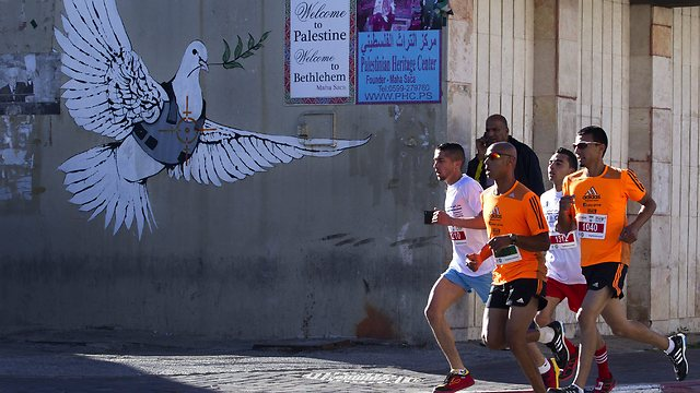 Running along West Bank separation fence (Photo: EPA)