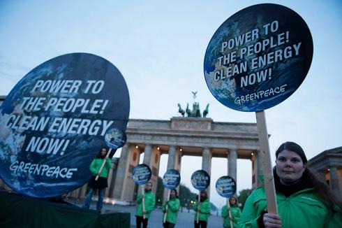 """""""כוח לעם, אנרגיה ירוקה עכשיו"""". פעילי סביבה בשער ברנדנבורג בברלין (צילום: רויטרס) (צילום: רויטרס)"""