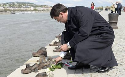 Hungarian President Janos Ader lighting candles in memory of the Holocaust on the Bnaks of the Danube River (Photo: EPA)