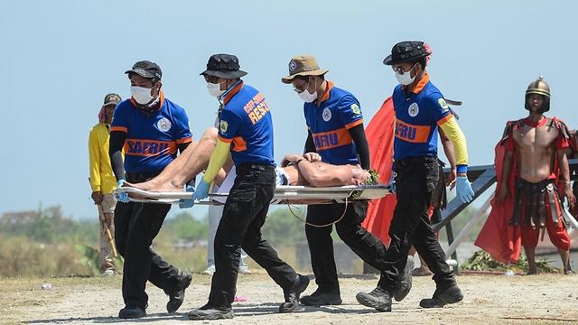 פינוי אחד הנצלבים לטיפול אחרי הטקס (צילום: Getty Images)