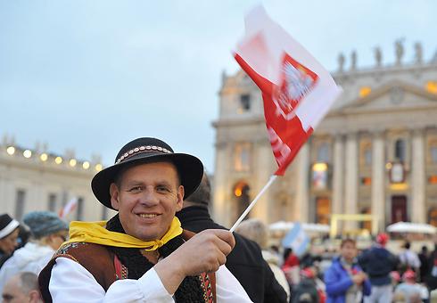 מאמין קתולי בוותיקן עם דגל פולין, ארץ הולדתו של יוחנן פאולוס ה-2 (צילום: AFP) (צילום: AFP)