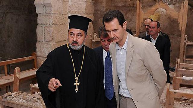 הנוצרים שנותרו בסוריה סובלים מנחת זרוען של התנועות האיסלאמיות. אסד בביקור בכנסייה בעיירה הנוצרית מעלולא (צילום: AP) (צילום: AP)