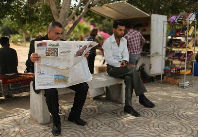Gaza man reading Al-Quds in a park (Photo: Reuters)