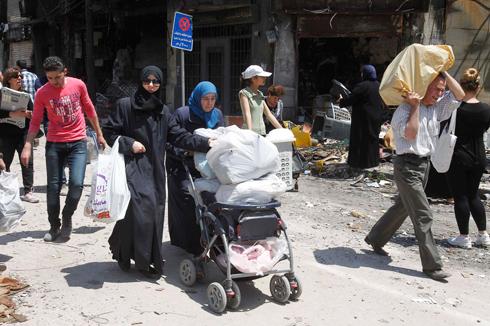 תושבים שבים לבתיהם אחרי תום המצור. חומס (צילום: רויטרס) (צילום: רויטרס)