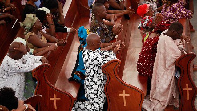 אולי התפילות יעזרו. מאמינים קתולים בכנסייה באבוג'ה (צילום: AP) (צילום: AP)