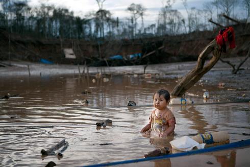 פריסאיידה בת השנתיים משתכשכת בלגונה מזוהמת. הוריה עובדים בכריית זהב (צילום: AP) (צילום: AP)