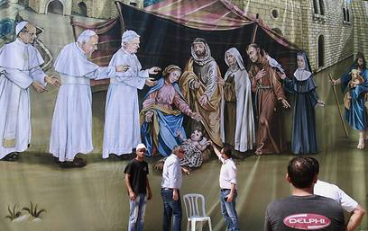 Banner depicting Jesus' birth with former popes Paul VI, John Paul II and Benedict XVI at Manger Square outside the Church of the Nativity (Photo: AP)