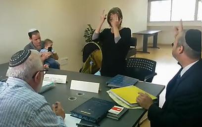 """מנדי תורג'מן מסיימת את טקס הגיור, בפני בית הדין. כך אומרים """"שמע ישראל"""" בשפת הסימנים (צילום: טלי פרקש) (צילום: טלי פרקש)"""